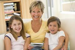 Grandmother reading with grandchildren. - stock photo