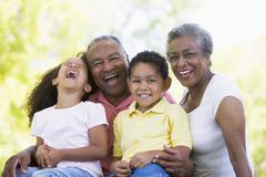 Grandparents laughing with grandchildren. Stock Photos