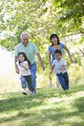 Grandparents running with grandchildren. - stock photo