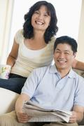 Couple relaxing with a newspaper and smiling - stock photo