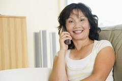 Woman sitting in living room using telephone and smiling Stock Photos