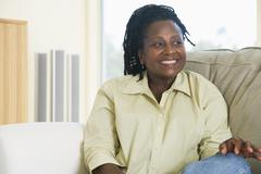 Woman sitting in living room smiling Stock Photos