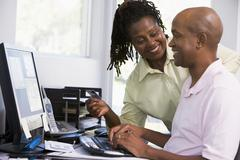 Couple in home office with credit card using computer and smiling Stock Photos