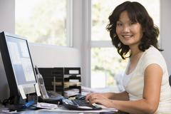 Woman in home office using computer and smiling Stock Photos