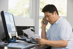 Man in home office with computer and paperwork on telephone Stock Photos