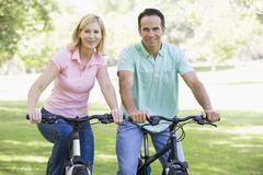 Stock Photo of Couple on bikes outdoors smiling