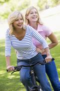 Stock Photo of Two friends on one bike outdoors smiling
