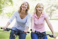 Two friends on bikes outdoors smiling Stock Photos