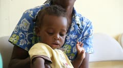 child on mother's lap in Haiti - stock footage