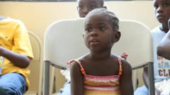 child waits for Dr. in Haitian clinic - stock footage