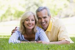 Couple relaxing outdoors in park smiling - stock photo