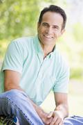 Man sitting outdoors smiling - stock photo