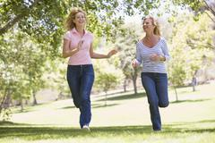 Two women running in park and smiling Stock Photos