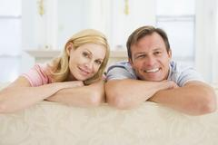 Couple relaxing in living room and smiling Stock Photos