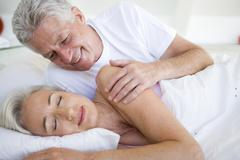 Man waking woman lying in bed sleeping - stock photo