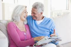 Couple with a magazine smiling - stock photo