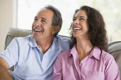 Couple relaxing in living room and laughing Stock Photos
