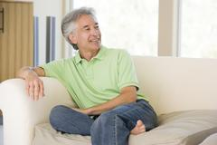 Man sitting in living room smiling - stock photo