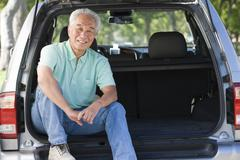 Man sitting in back of van smiling - stock photo