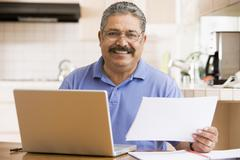 Man in kitchen with laptop and paperwork smiling - stock photo
