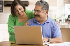 Couple in kitchen with laptop smiling Stock Photos