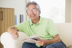 Man relaxing with a newspaper smiling - stock photo