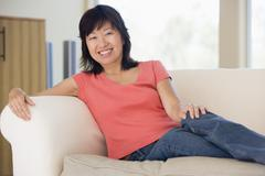 Woman relaxing in living room smiling - stock photo