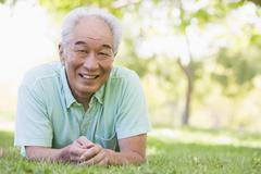 Man relaxing outdoors smiling - stock photo