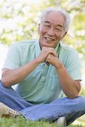 Man sitting outdoors smiling - stock photo