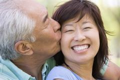 Couple relaxing outdoors in park kissing and smiling Stock Photos