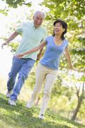Couple running outdoors in park by lake smiling Stock Photos