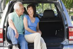 Couple sitting in back of van smiling - stock photo
