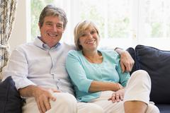 Couple relaxing in living room smiling - stock photo