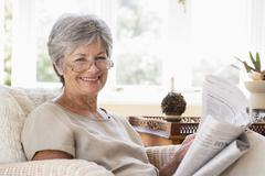 Woman in living room reading newspaper smiling - stock photo