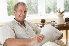 Man in living room reading newspaper smiling - stock photo