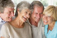 Two couples indoors smiling - stock photo