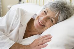 Woman lying in bed smiling Stock Photos