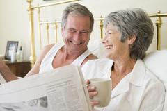 Couple in bedroom with coffee and newspapers smiling - stock photo