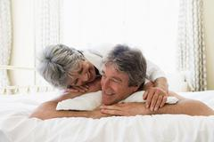 Couple relaxing in bedroom and smiling - stock photo