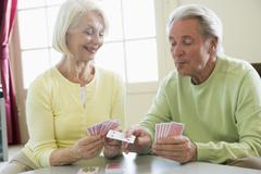 Couple playing cards in living room smiling - stock photo