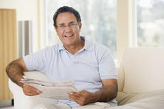 Man in living room reading newspaper smiling Stock Photos