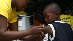 Young Haitian boy receives vaccination shot Stock Footage