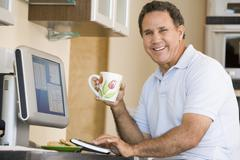 Man in kitchen with computer and coffee smiling - stock photo
