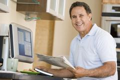 Man in kitchen with computer and newspaper smiling - stock photo