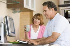 Couple in kitchen with computer and coffee smiling - stock photo