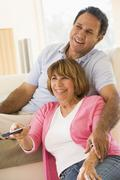 Stock Photo of Couple in living room with remote control smiling