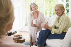 Three women in living room with coffee smiling - stock photo