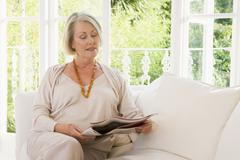 Woman in living room reading newspaper - stock photo