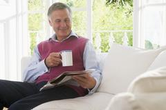 Man in living room with coffee reading newspaper smiling - stock photo