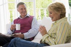 Couple in living room with coffee and newspaper smiling - stock photo